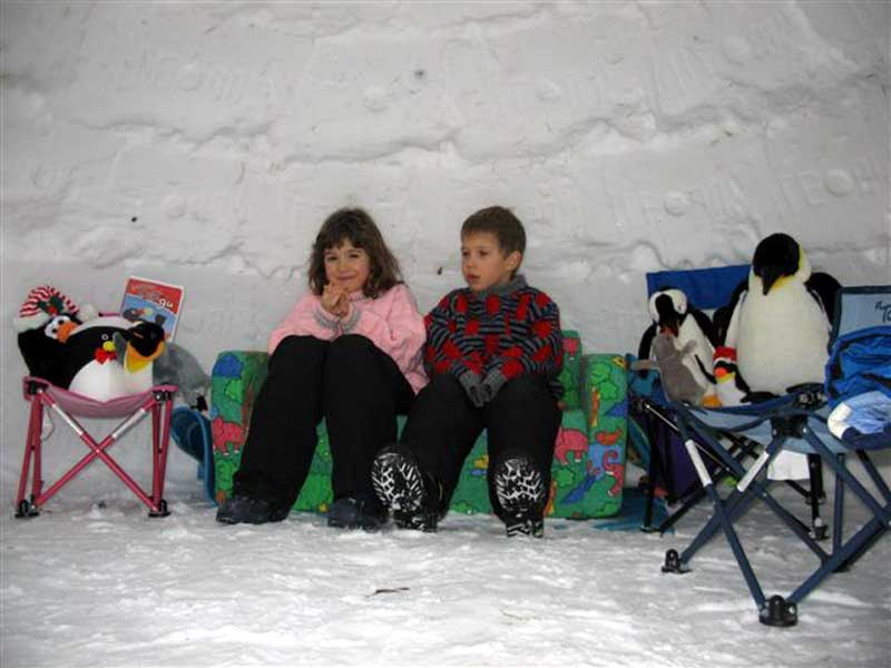 Two small children relaxing in an igloo.