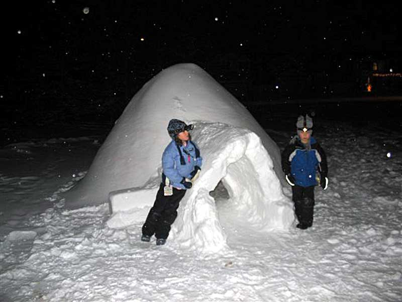 Two kids build an igloo with covered entrance.