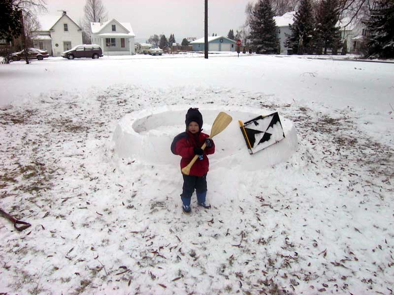 Small child learning how to build an igloo.